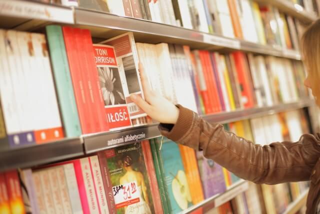 入門用の韓国語テキストを本棚から選んでいるイメージ