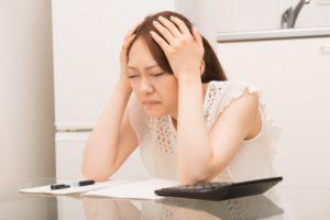 キッチンのリフォーム費用が予算とかけ離れてしまい頭を抱えている主婦のイメージ